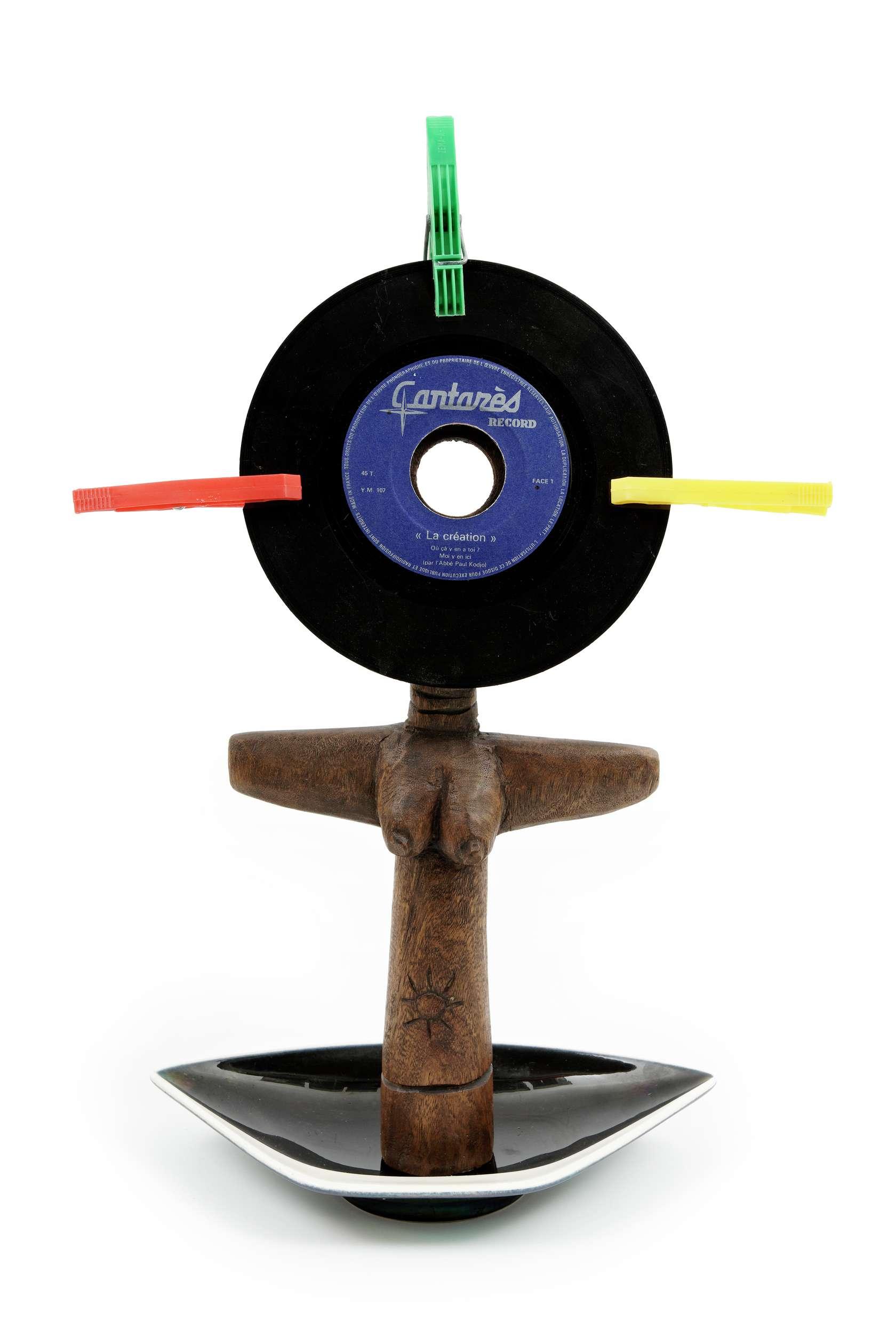 Présence Panchounette, Ashanti de faire votre connaissance, 1985 Statue en bois exotique, cendrier en faïence, disque vinyl 45tr (la création du père Kodjo) et pinces à linge44 × 30 × 10 cm / 17 3/8 × 11 6/8 × 3 7/8 in.