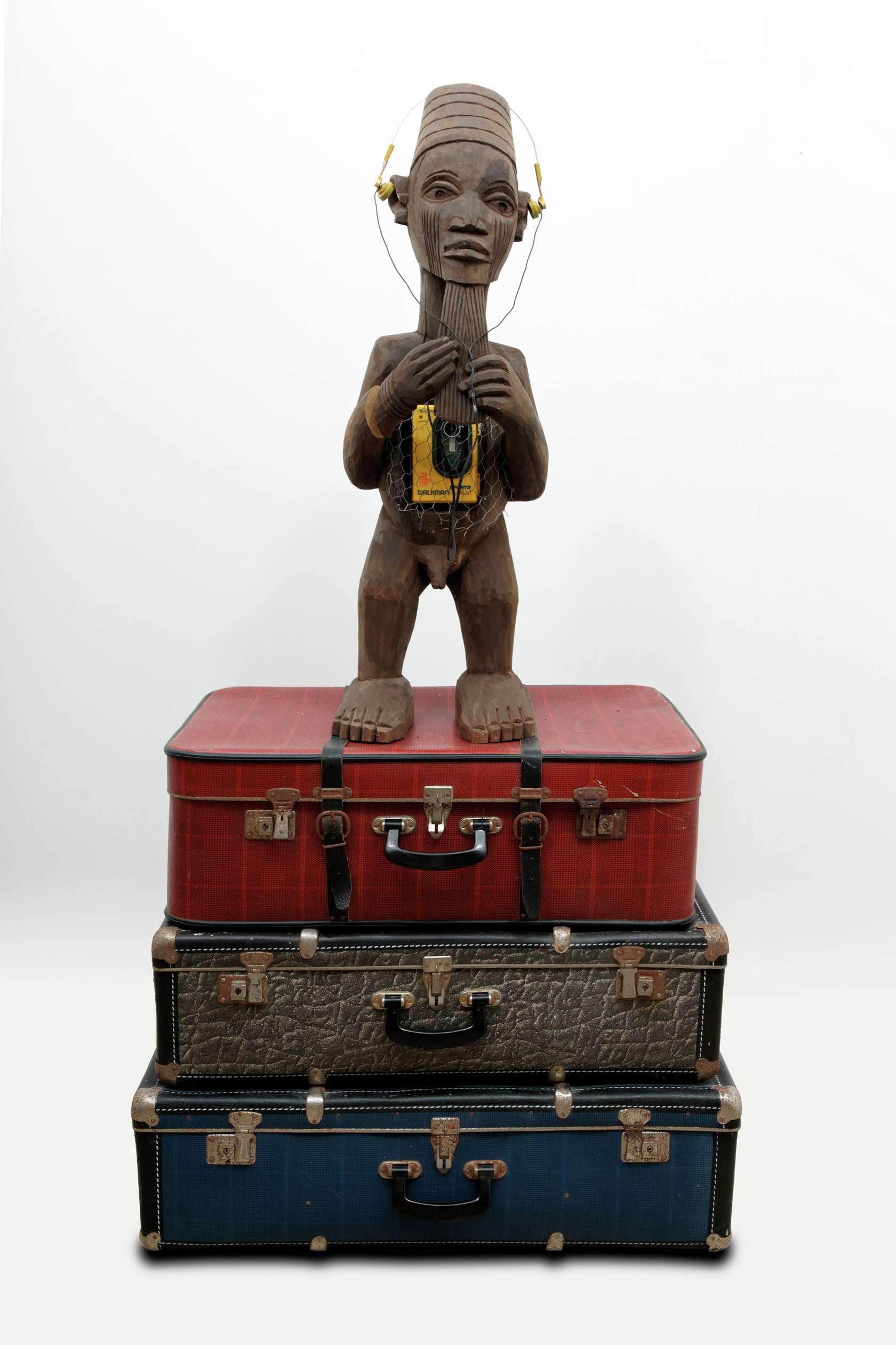 Présence Panchounette, Bateke (walkman), 1985 Statue en bois exotique, grillage, walkman et valises158 x 80 x 55 cm / 62 2/8 x 31 1/2 x 21 5/8 inches