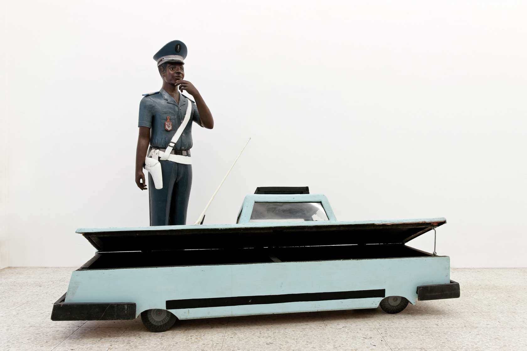 Présence Panchounette, Traffic, 1985 Mercedes-cercueuil en bois peint (par Kane Kwei), statue en bois peint (par Nicolas Damas), statuettes touristiques d'éléphants et baladeurCerceuil / Coffin 57 × 205.5 × 52.5 cm / 22 1/2 × 80 7/8 × 20 5/8 in.Sculpture 168 × 53 × 48 cm / 66 1/8 × 20 7/8 × 18 7/8 in.