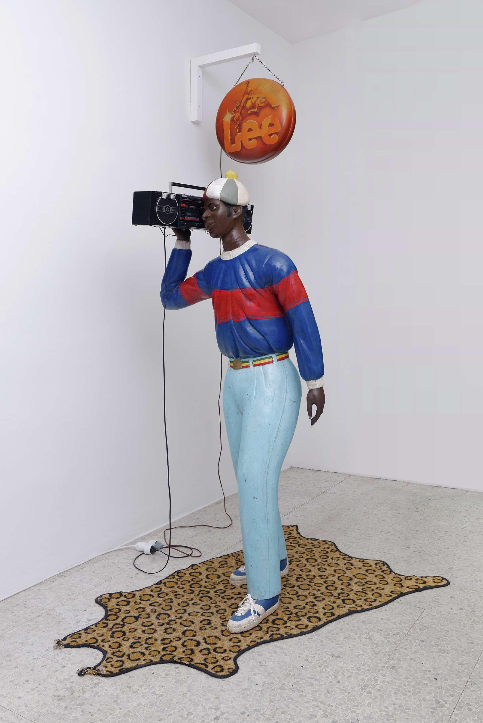 Présence Panchounette, Disco Boy, 1985 Sculpture en bois peint (Nicolas Damas), ghetto blaster et cassette audio, tapis, enseigne lumineuse