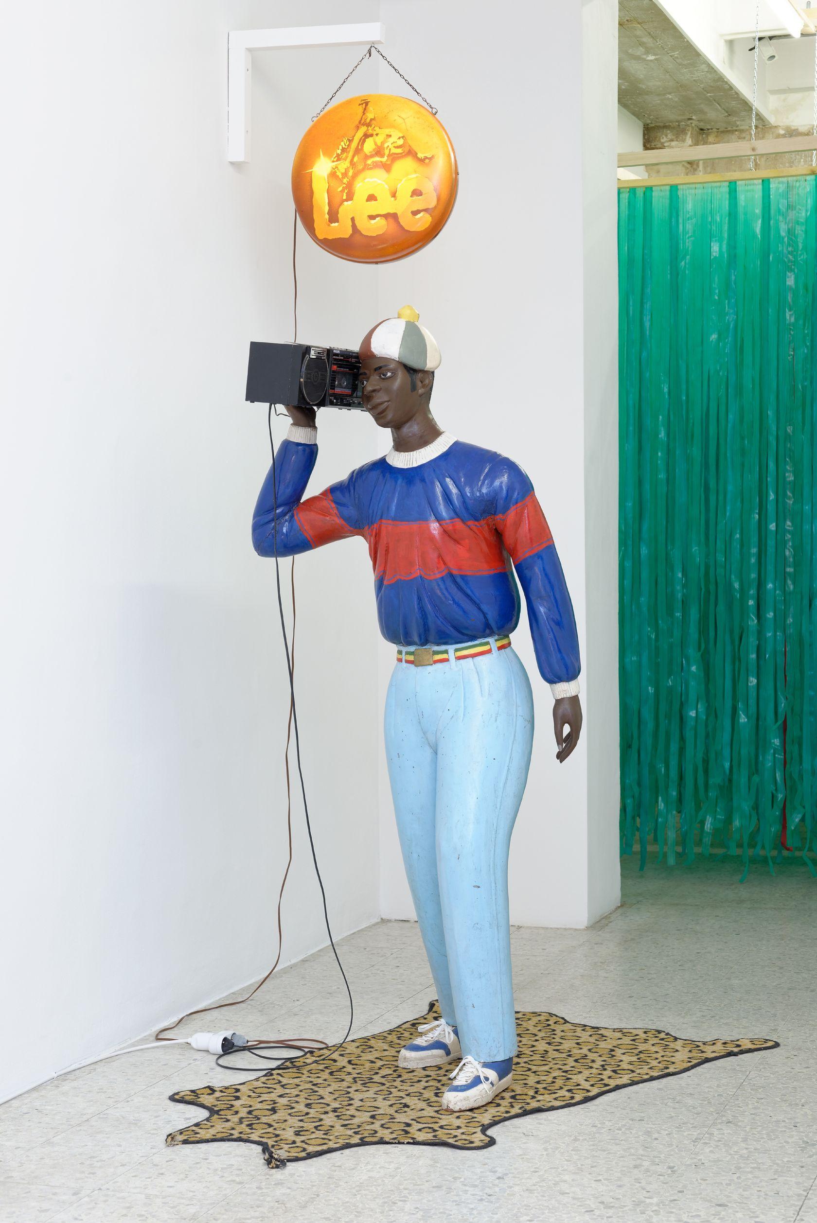 Présence Panchounette, Disco Boy, 1985 Sculpture en bois peint (par Nicolas Damas), ghetto blaster et cassette audio, tapis, enseigne lumineuse174 × 68 cm / 68 1/2 × 26 6/8 in.